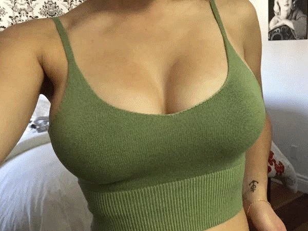 Android App Icon coming out from olive green knitted thin strap sports bra of a sexy model
