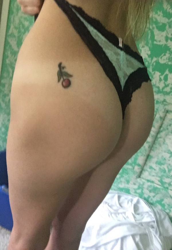 Sexy blonde showing her nice round butt with red cherry tattoo taking a bum selfie in whiite thong with black lace border.