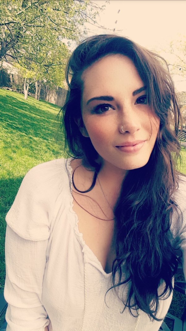 Cute brunette with nose ring takes selfie in white top