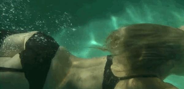 Sexy girl in black net bikini top and black lace thong doing underwater swimming. gif