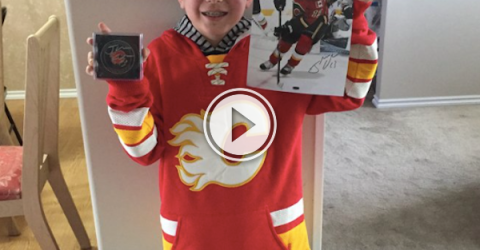 Kid in red jersey holds the poster of his favorite ice hockey player!