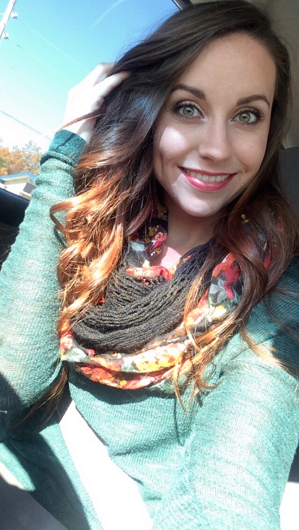 Brunette with light eyes smiles for selfie in blue top