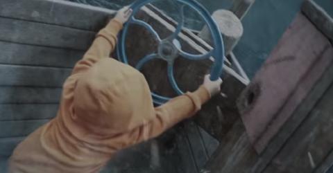 Kid in brown hoodie manning the steering wheel in a boat.