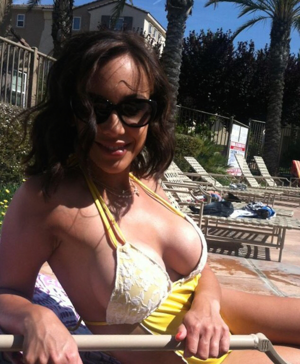 Sexy woman showing her large busty boobs while wearing white-yellow, double strap bikini top and stylish black sunglasses while sitting on a pool side chair