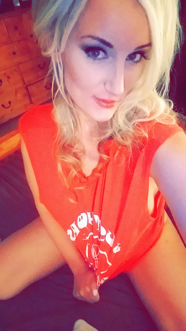 blonde looking very sexy in bright orange top, deep black eyes with heavy eyelashes, golden hair. orange juicy lips