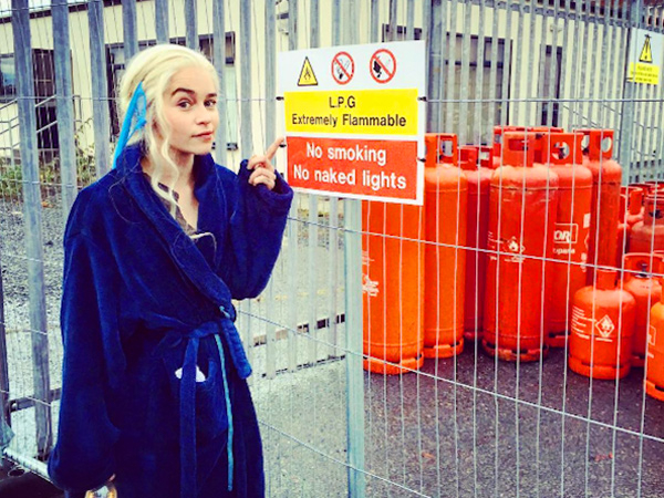 Emilia Clarke in blue bathrobe pointing to a danger sign