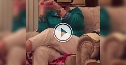 Screenshot of a video with an old woman whose eyes are tied up by a mobile phone
