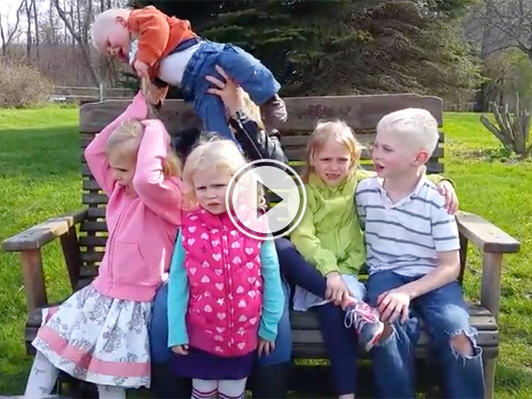 A family with five kids pose for a photo on a park bench!