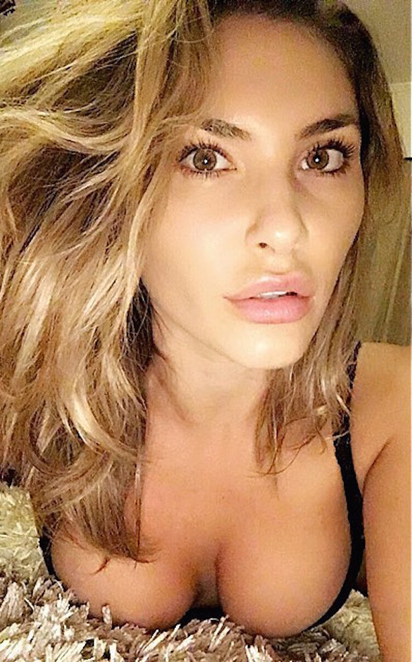 Light-eyed blonde with full lips and perky boobs takes selfie in black bra
