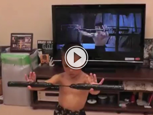 A kid giving the same pose as Bruce Lee on the TV behind him, titled 'Meet Bruce Lee's Mini'. (VIDEO)