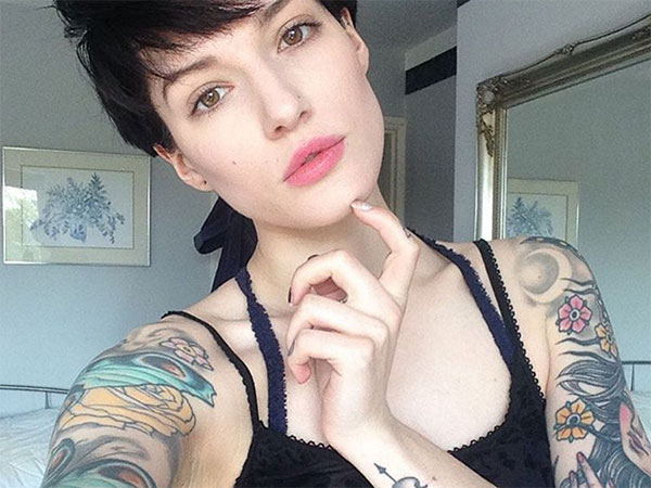 Light-eyed cropped hair brunette with tattoos takes a selfie in black lace top!