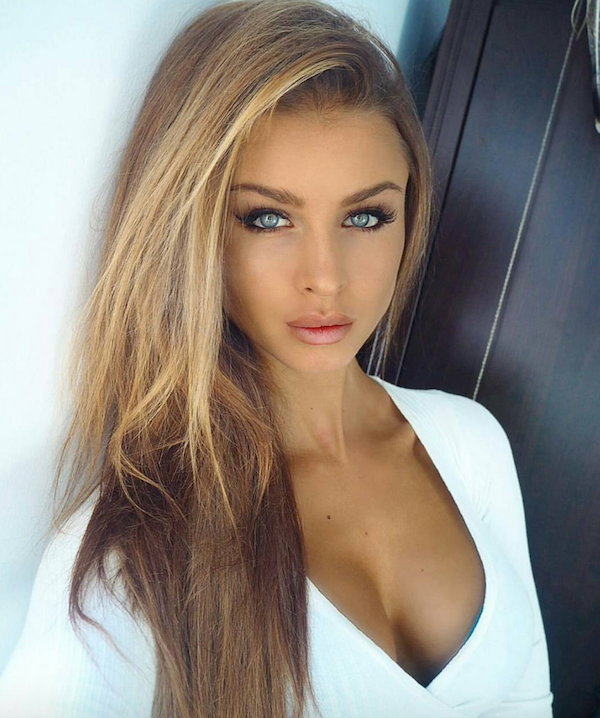Cute blonde with grey eyes and full lips takes selfie in perky cleavage showing white top
