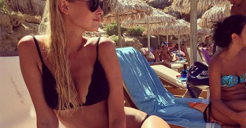 Blonde with sexy curvy body and perky boobs poses at beach in black bikini