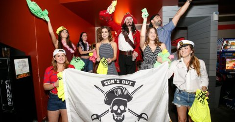 The pirate captain pose with his flag held by other drunk passengers in a party