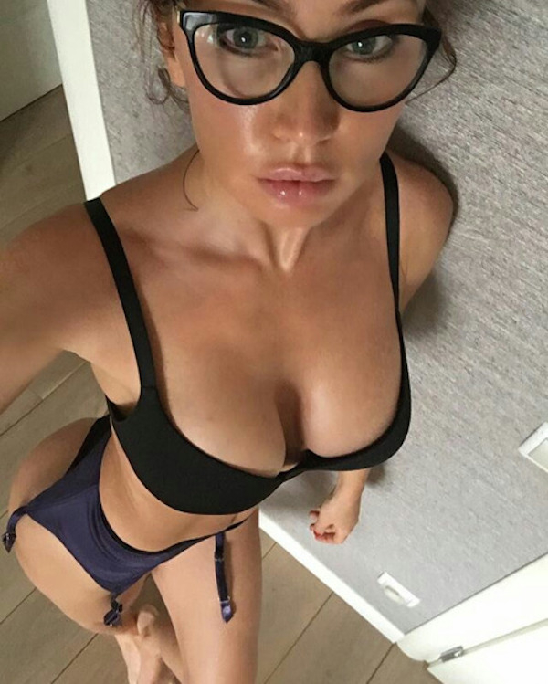 Light-eyed blonde in glasses takes selfie of perky boobs and sexy body in black and purple lingerie