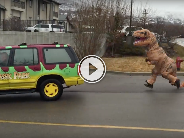 Dude in a T-Rex costume chases a Jurassic Park colored van!