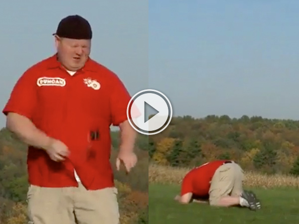 An overweight dude in beige shorts and blue shirt kneeling on green grass with his face down!