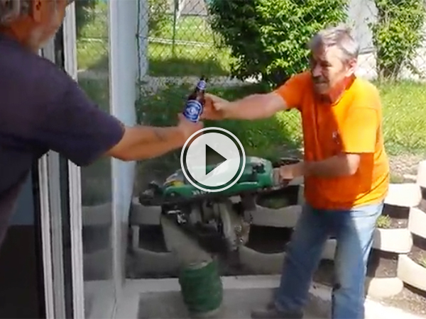 Man in orange tee and blue jeans accepts a bottle of beer from another man!