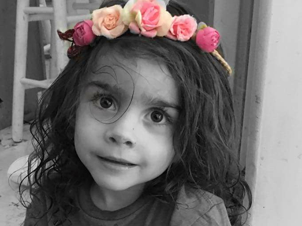 Kid girl with big eyes and flowers on her head looks into the camera!