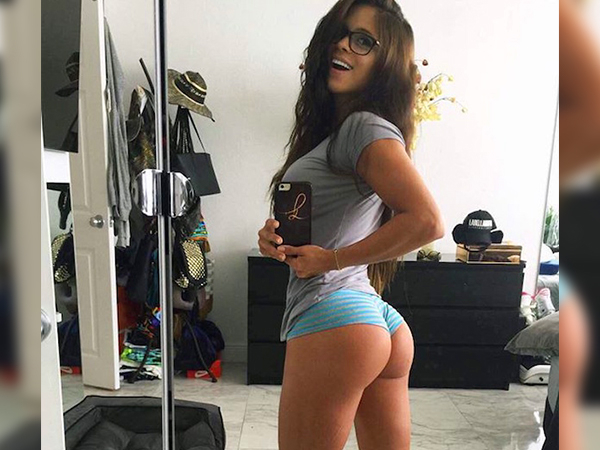 Girl with big boobs twists to take a mirror selfie wearing a grey top and blue panty