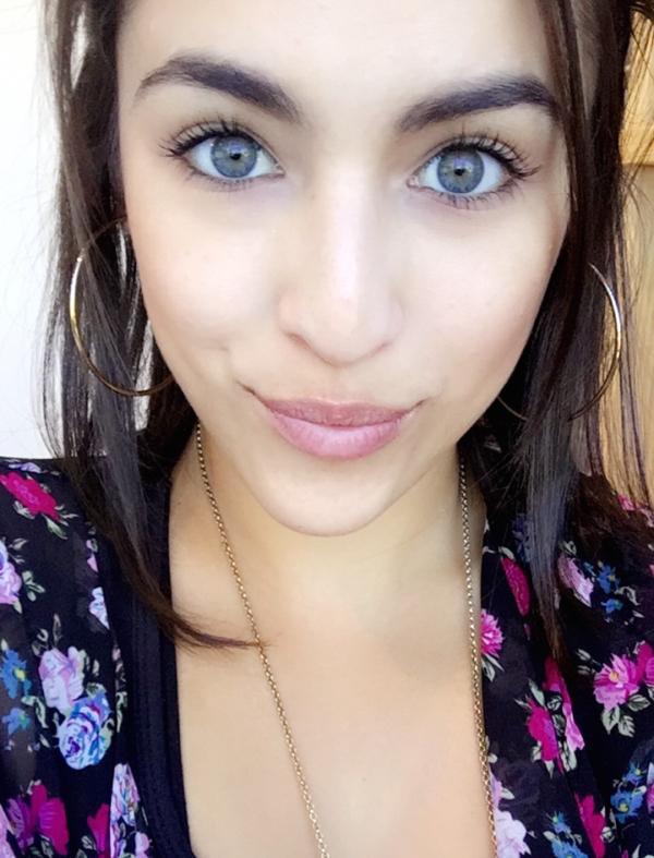 Cute brunette with light grey eyes takes selfie in flowery black dress