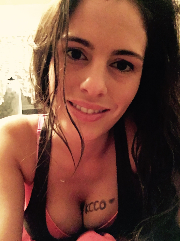 Brunette with perky boobs takes selfie in red bra and black vest with KCCO written on cleavage