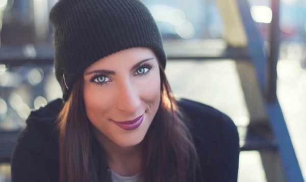 Brunette with cat eyes smiles for camera in black beanie, grey tee, and black hoodie