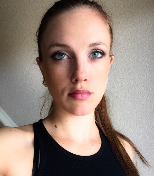 Girl with blue eyes and plump lips takes selfie in black tank top