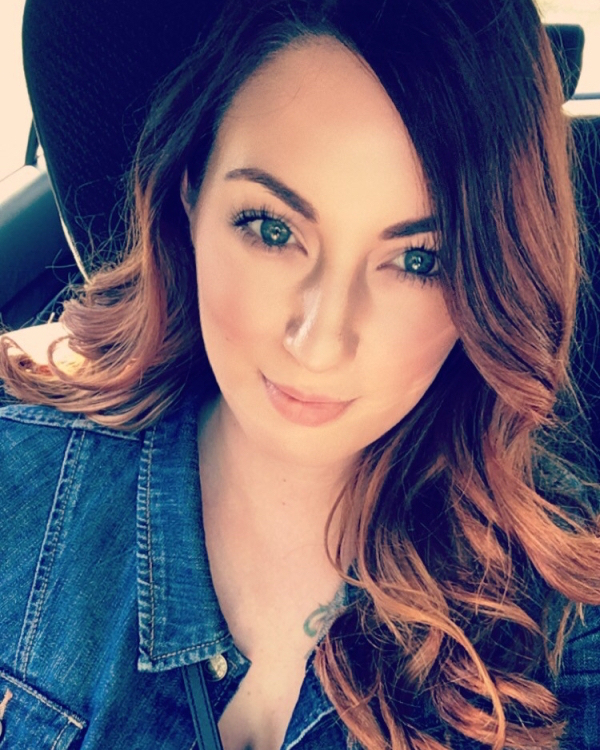 Beautiful brunette with blue eyes takes selfie in car in blue denim shirt
