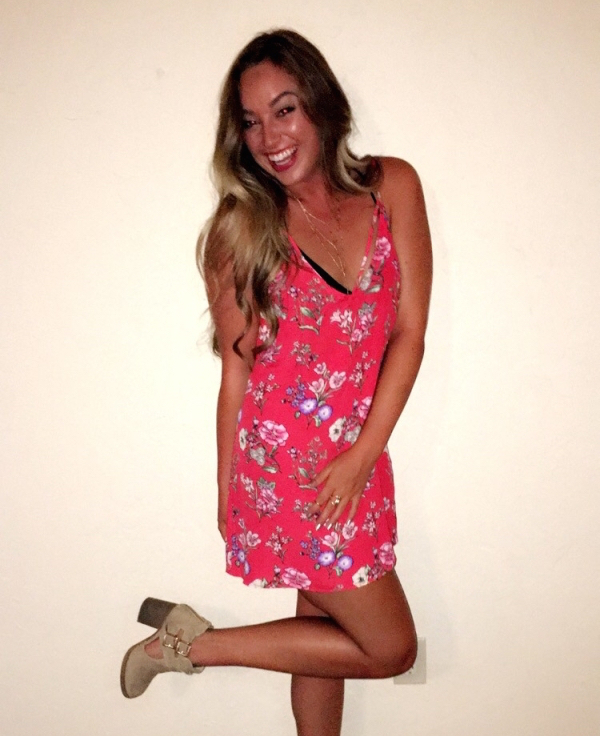 Blonde with sexy body smiles for camera in flowery red dress