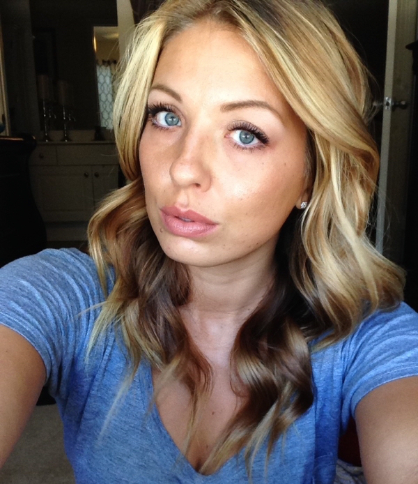 Blonde with light eyes and full lips takes selfie in blue tee