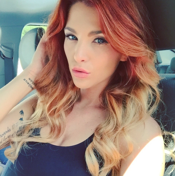 Dyed redhead with blue eyes and wavy tresses takes selfie in blue tank top