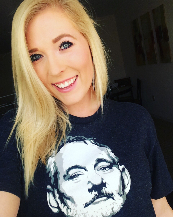 Blonde with light eyes smiles for a selfie in black tee with Bill Murray portrait
