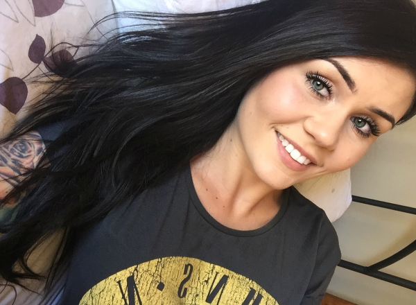 Cute brunette with flowing tresses and light eyes takes selfie in black tee