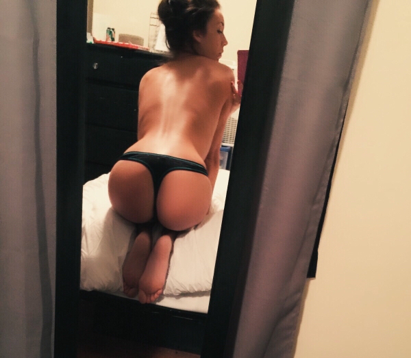 Topless brunette takes selfie of round butt cheeks, bare back, and curvy body in black thong