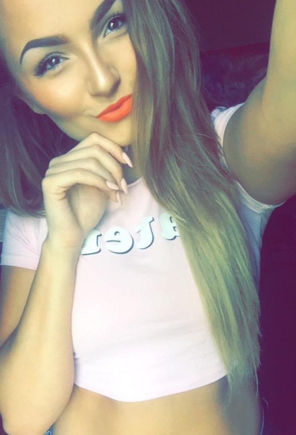 Cute blonde with flowing tresses takes selfie in crop pink top