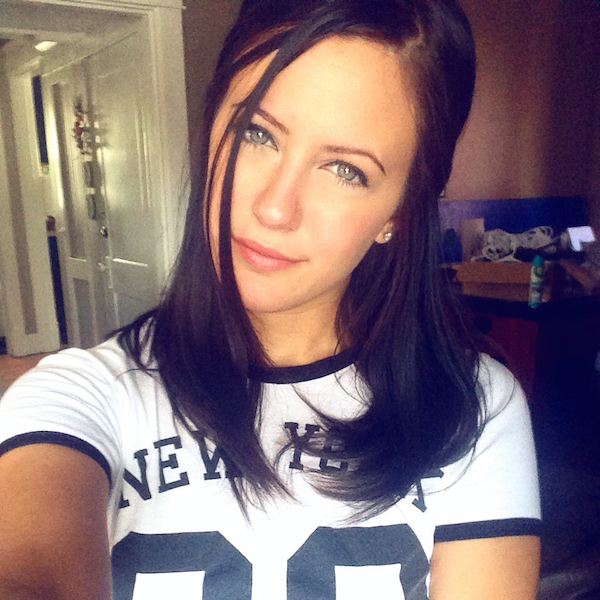 Beautiful brunette with light eyes takes selfie in white tee