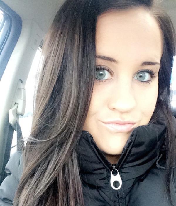 Brunette with light eyes takes selfie in car in black jacket