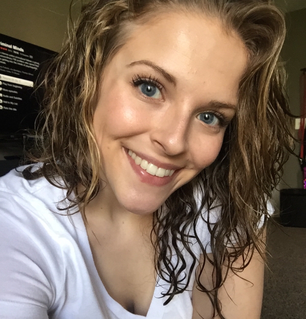 Blonde with light-grey eyes smiles for selfie in white tee