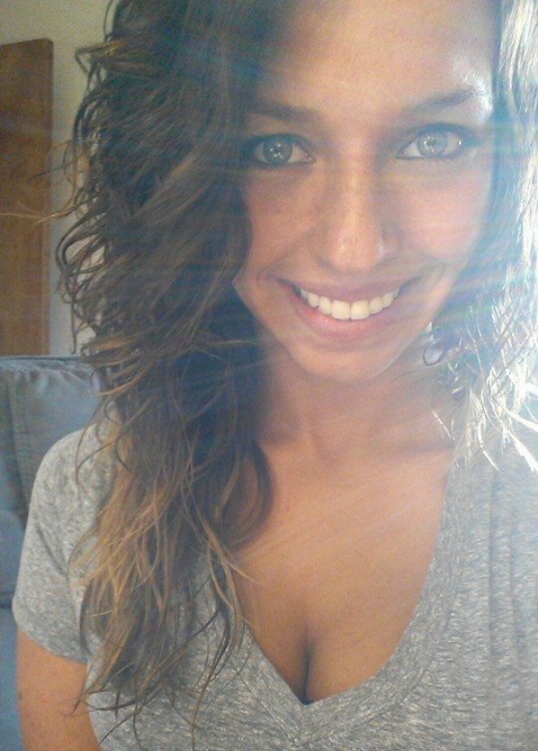 Light-eyed girl with wavy tresses takes selfie in perky cleavage showing grey tee