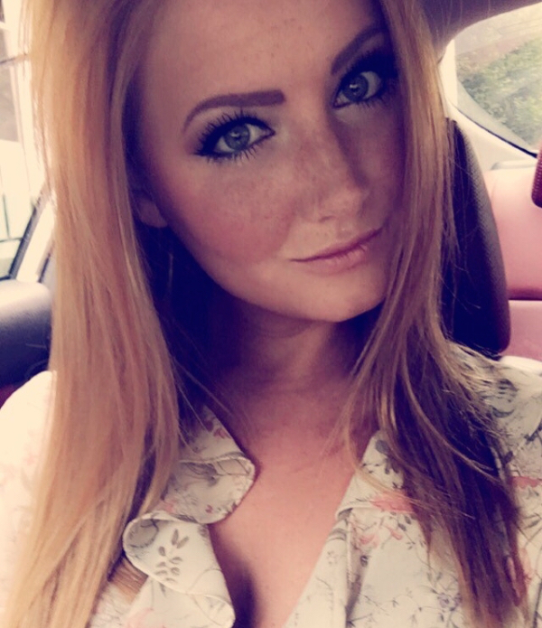 Beautiful light-eyed blonde with freckles takes selfie in white printed top