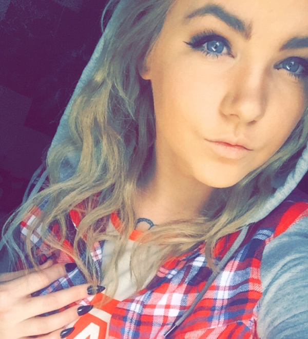 Light-eyed blonde girl takes selfie in white tee and red checked shirt