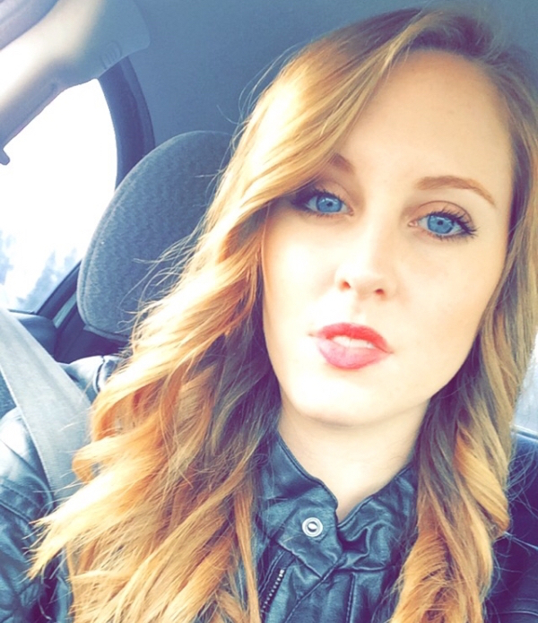 Blonde with blue eyes and full lips takes selfie in black jacket in car