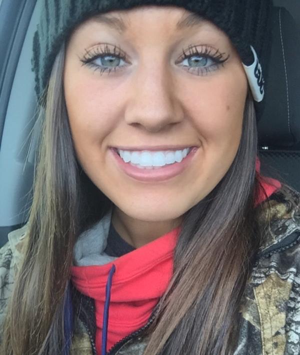 Light-eyed brunette smiles for selfie in black beanie cap and printed jacket