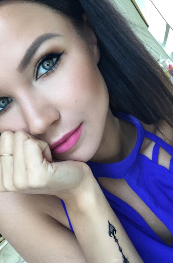 Gorgeous light-eyed brunette with flawless skin takes selfie in blue top