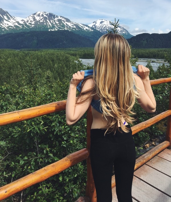 Blonde in black jeans and blue top flashes snow capped mountains and lush jungles