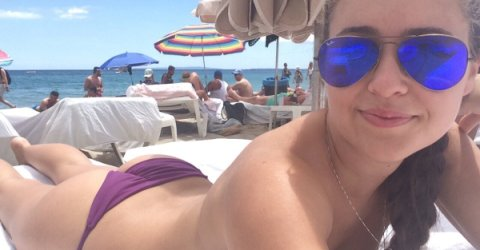 Topless girl in blue RayBan Aviators relaxing on her boobs wearing purple panties smiles for the photo