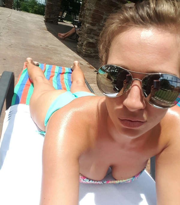 Blonde tanning on bed takes selfie of cute butt and perky boobs in cleavage showing blue bikini