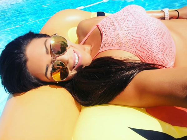 Brunette with supple boobs poses in sunglasses and pink bikini top on float in pool