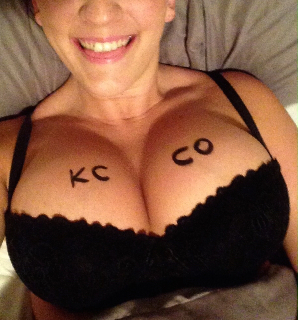 Woman with KCCO written on knockers smiles for camera in big cleavage showing black bra